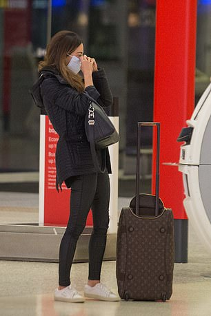 Luxury: Showing off her expensive taste, she pulled along a $4,000 Louis Vuitton suitcase
