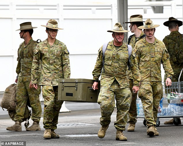 The military has been deployed to help enforce Australia's quarantine rules. All travelers were required to isolate themselves for 14 days. Soldiers are pictured awaiting the arrival of foreign passengers at Sydney Airport on March 30.