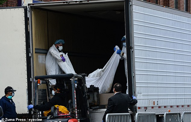 New York hospitals were forced to use sheets to wrap the bodies because they no longer had body bags. Bodies are pictured being loaded onto a truck outside the Brooklyn Hospital Center on March 31