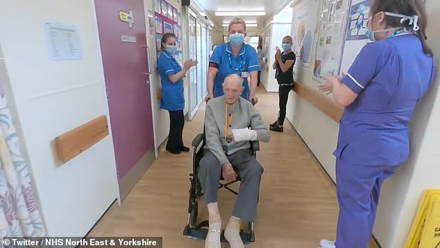 Staff line the corridors and clap while Mr Chambers is pushed out in a wheelchair
