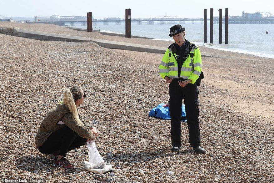 Un oficial de policía camina por la playa de Brighton pidiéndole a la gente que se mueva durante el encierro de coronavirus este Viernes Santo