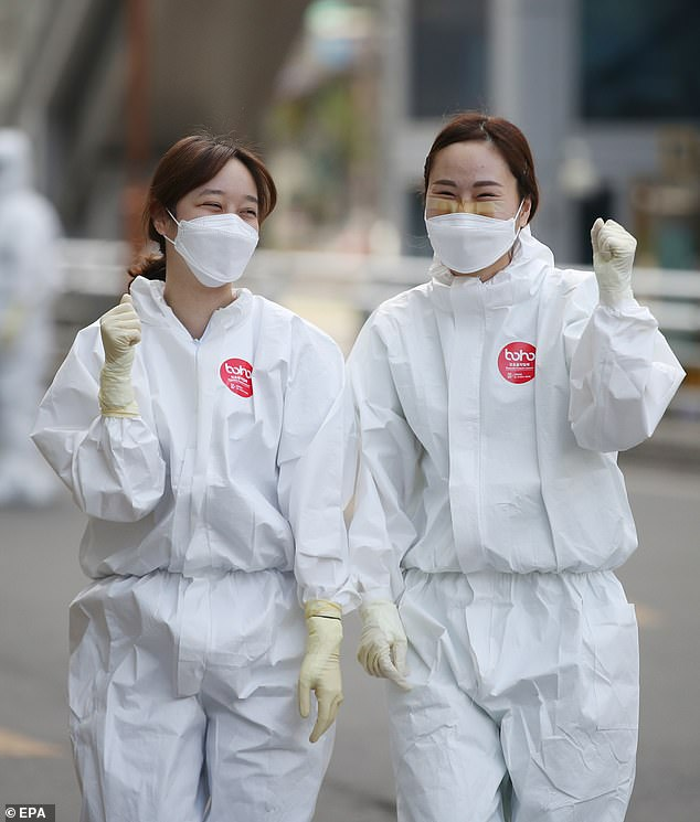 Medical workers gesture as they enter a hospital for a shift, in Daegu, March 30, 2020