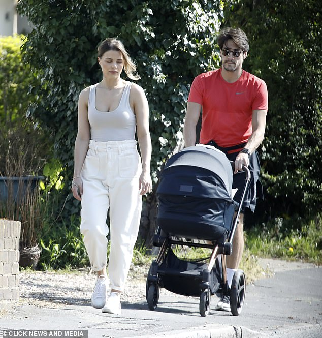 Strolling: Former TOWIE star looked sensational in a tight gray tank top with white high waisted jeans while her boyfriend pushed their baby's stroller