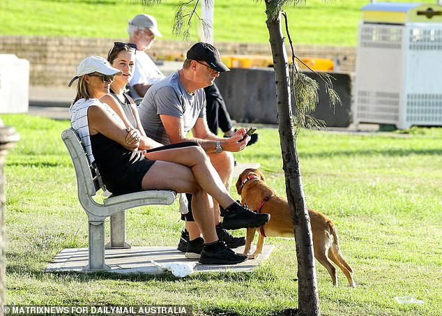 Australians are requested not to pet anyone unless they have washed their hands first and after. In the photo, Sydneysiders and a four-legged friend receive their daily dose of fresh air on Saturday