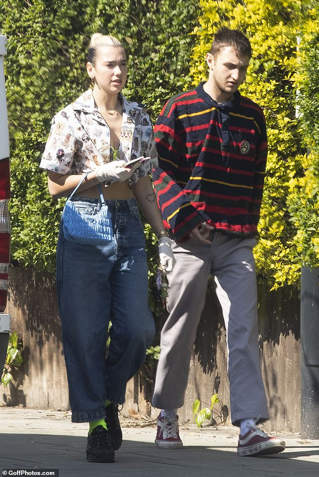 Edgy: Dua wore a casual but offbeat look, pairing a pair of baggy flare jeans with a short printed shirt