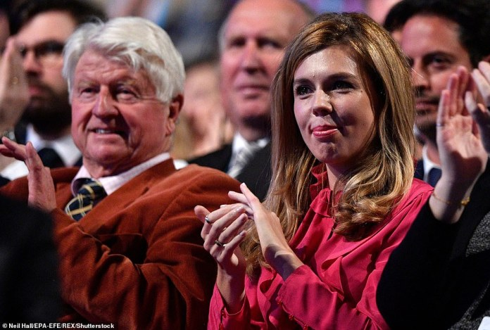 Stanley Johnson (L) and Carrie Symonds (R), father and girlfriend of British Prime Minister Boris Johnson, watch as he delivers his opening speech at the Conservative Party Conference