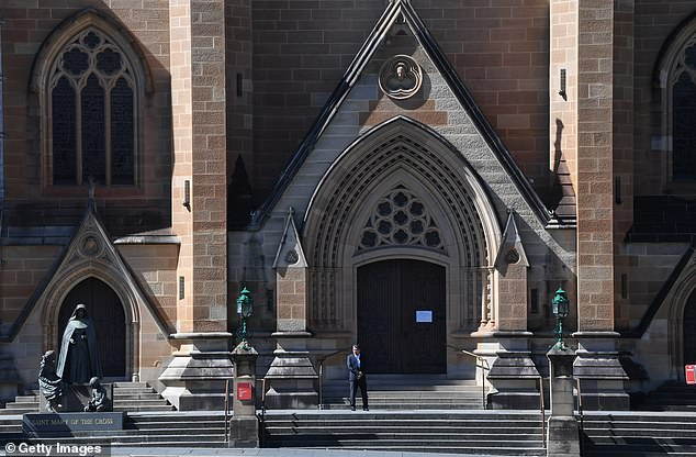 A security guard stands outside the quiet St Mary's Cathedral in Sydney where there is no Easter service held for people to be present on April 12. Danish political scientist Dr Bjorn Lomborg said Australia could benefit from following the relaxed pace of Swedish social long-distance steps.