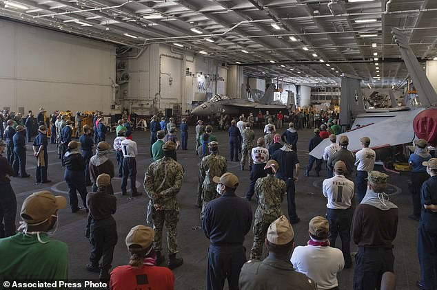 In this photo taken April 7 2020, provided by the U.S. Navy, sailors and staff assigned to the aircraft carrier USS Theodore Roosevelt listen as Vice Adm. William Merz, commander of the U.S. 7th Fleet, answers questions during a visit to the ship at Naval Base Guam