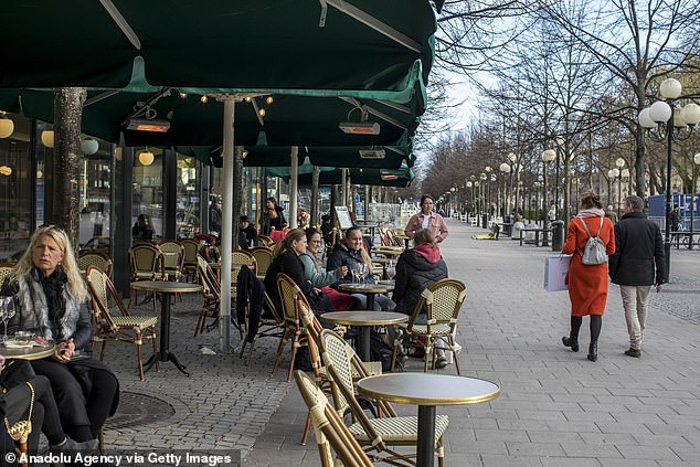 People hang out in a cafe in central Stockholm in the middle of the pandemic. In an opt-ed Tuesday, some 22 public health experts called on politicians to take control, saying the Swedish Public Health Agency had failed