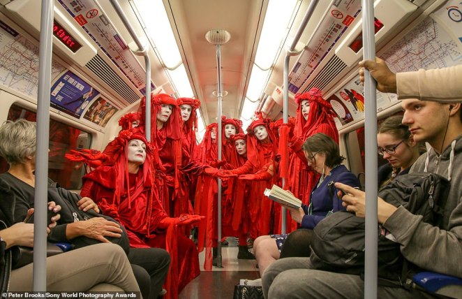 This unusual image was captured by British photographer Peter Brooks on the London Underground in October 2019 during the Extinction Rebellion uprising. He was shortlisted in the street photography category. He said: 'This image is part of my efforts to capture the emotional impact the Red Rebel Brigade had on the public, and the protests, through conversation and photography'