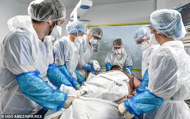 A team of medical workers wearing protective suits and masks attend to a coronavirus patient in intensive care at a hospital in France yesterday