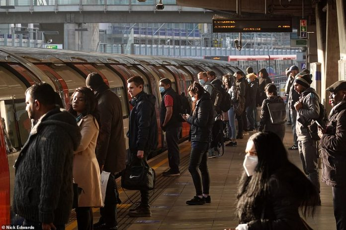 In Canning Town, east London, workers lined up while waiting to board the tubes. The station is in zone 2/3 of the TfL network