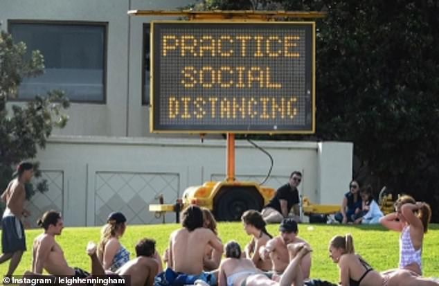 These sunbathers, in Victoria, Australia, seem to be completely oblivious to the giant sign behind them warning people to 'practice social distancing'