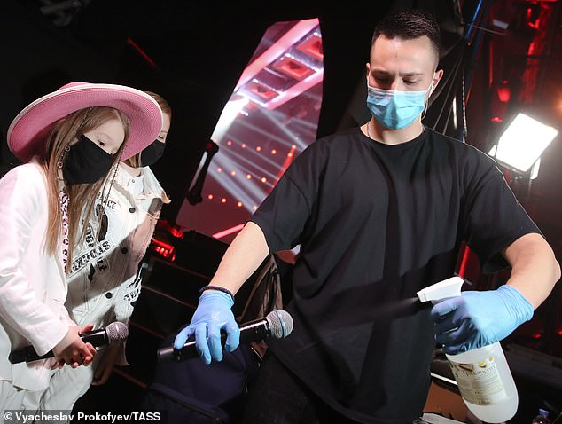 Acts: The acts also wore masks and a crew member is seen sterilizing the microphone