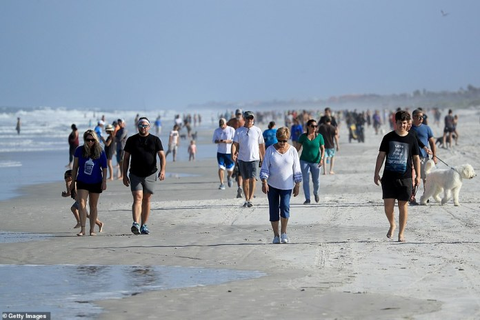 People are seen at the beach Friday in Jacksonville Beach, Florida. Beaches have reopened but only during limited hours and can only be used for swimming, running, surfing, walking, biking, fishing and pet care