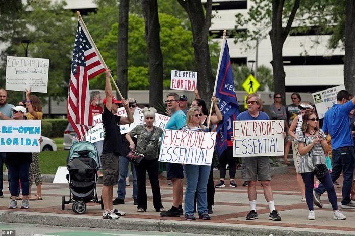 Vendredi, à Orlando, des manifestants brandissent des pancartes indiquant «Re-Open Florida» et «Everyone's Essential»
