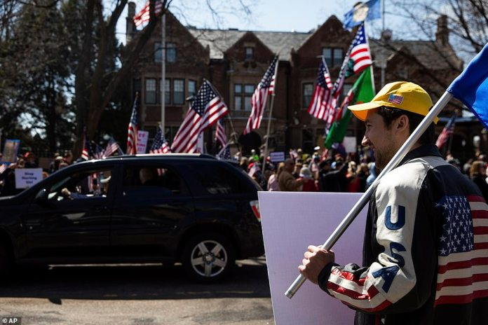 A protester (right) wears a jacket with an American flag with his back at the demonstration in Saint Paul on Friday