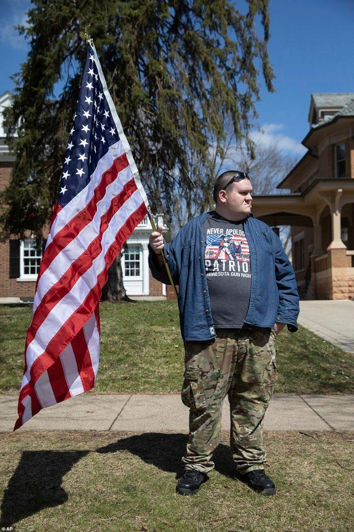Un homme portant un t-shirt avec un message sur les droits des armes à feu est titulaire d'un drapeau américain lors de la manifestation à Saint-Paul vendredi
