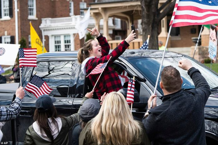 A woman leans out of the window of her truck to take a selfie with other protesters during the 'Liberate Minnesota' demonstration in St. Paul Friday