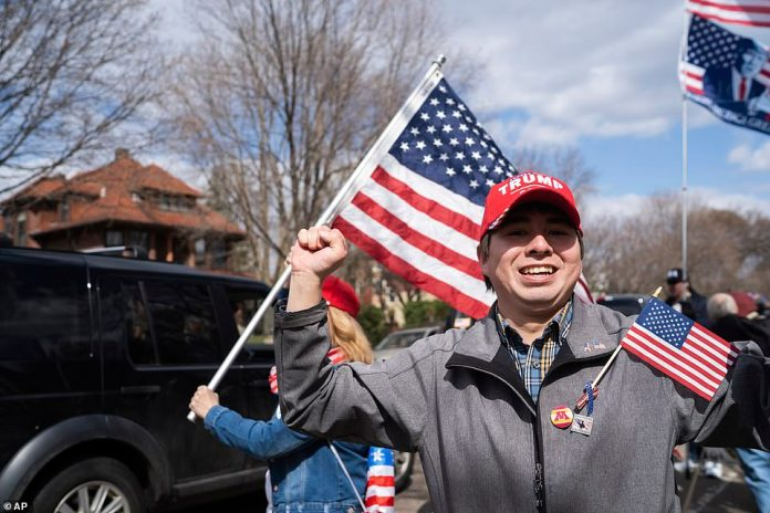 Man wearing red pro-Trump hat attends protest in St. Paul, Minnesota, Friday