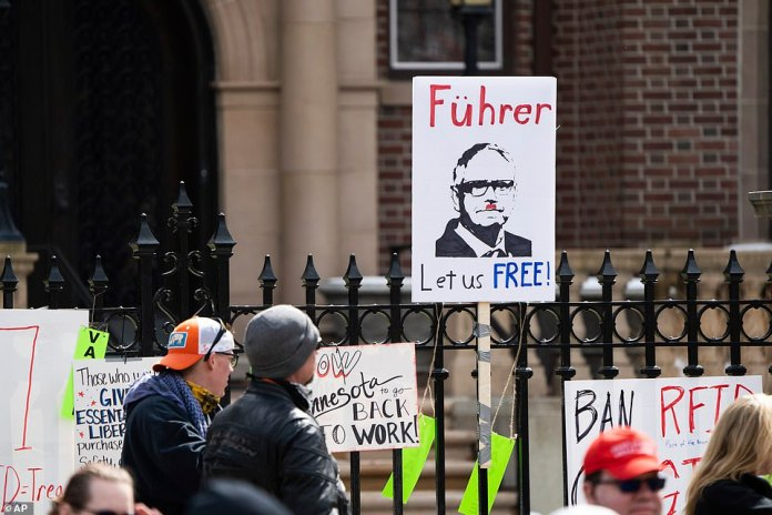 A panel attached to the fence outside the governor's residence compares Walz to Adolf Hitler