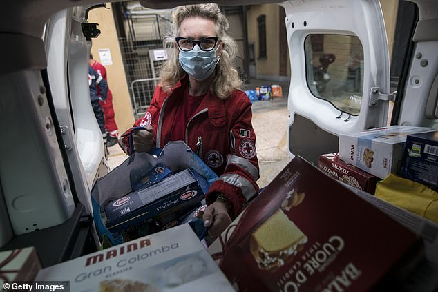 Italy is watching the barrel of the worst recession since the Second World War. Pictured: Red Cross volunteers load boxes of food to deliver as donations to families in need during the current Turin coronavirus crisis