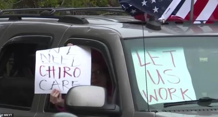 'Let us work,' one sign displayed from inside a vehicle in Frankfort read on Friday