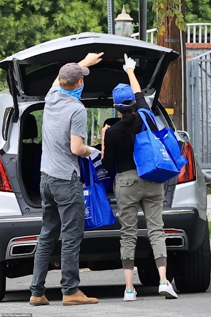 Harry and Meghan worked together to remove packages from the back of their $ 35,000 Cadillac XT5