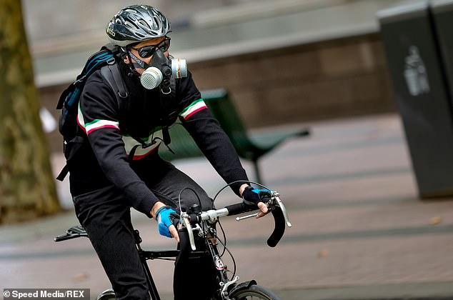 Large live sporting events such as football and cricket are expected to remain closed to spectators. Pictured: A cyclist in a valved gas mask in Melbourne on Saturday