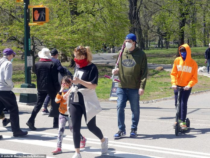 On Sunday, we saw families taking a walk in the park. Some appear in front of a sign warning people of social distance