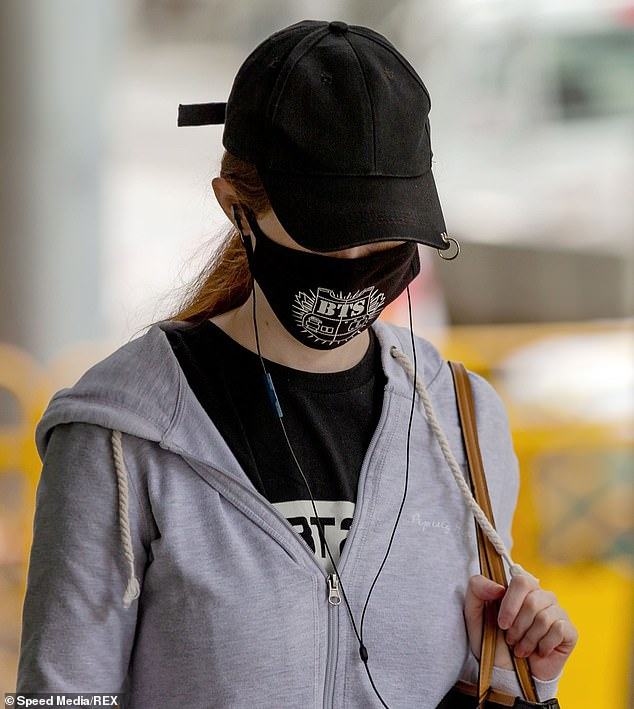 A woman wears a black face mask in Melbourne on Saturday. About one in six Australianswear a face mask whenever they leave home, according to survey findings released on Monday