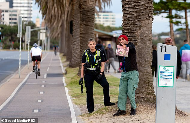 A Melbourne Police officer is pictured questioning a pedestrian to ensure he is not breaking the social distancing rules brought in to slow the spread of COVID-19