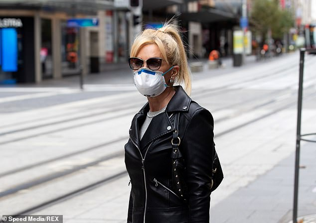 A woman in a leather jacket is pictured wearing face mask while shopping on George Street in Sydney on Monday