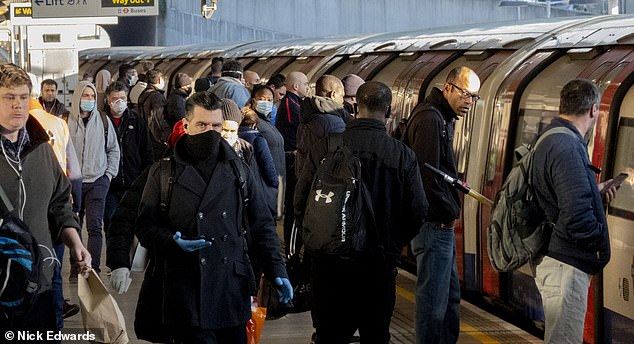 Crowds of commuters board a Jubilee line train at Canning Town station on the London Underground yesterday morning