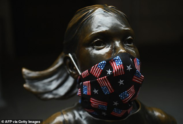 The statue of 'Fearless Girl' wears a facial mask with American flags outside the New York Stock Exchange on Wall Street yesterday