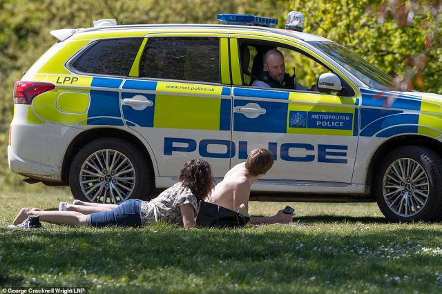 Police speak to sunbathers as they patrol Greenwich Park in London this afternoon. Under guidelines, you are only supposed to leave your home for exercise
