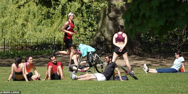 Londoners in Green Park also enjoyed the sun. Seven people were pictured sitting near each other as a runner jogged past