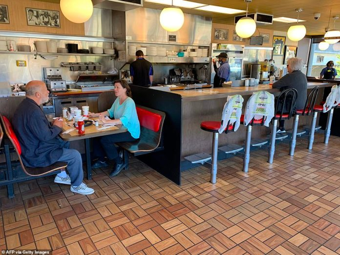 Customers sit for breakfast at a waffle house in Atlanta as the U.S. state of Georgia eases restrictions on April 27