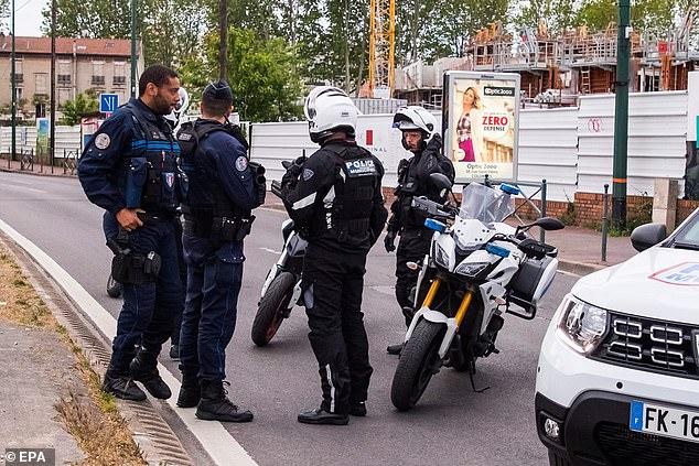 Des policiers français à moto sécurisent un périmètre de sécurité à Colombes sur les lieux de l'attentat terroriste présumé