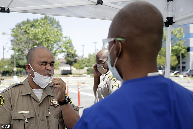 A Los Angeles sheriff takes a COVID-19 test on Monday using a swab. President vowed to get more swabs from states for coronavirus testing