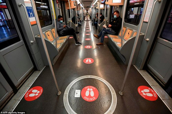 Commuters on a train in Milan with stickers on the ground indicating where people should stand and on the seats, indicating how far people should sit from each other