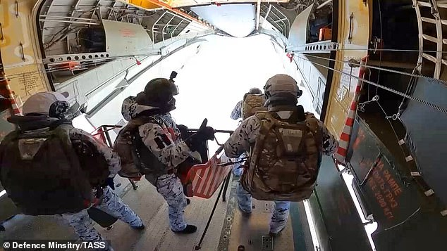 Russian paratroopers wearing oxygen masks and white camouflage jumped 33,000ft out of a plane over the Arctic as part of a war games exercise
