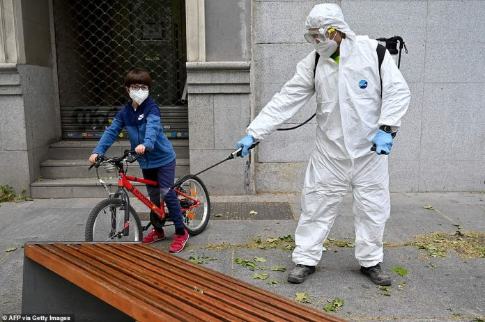 A boy wearing a face mask rides his bike next to a worker disinfecting a bench in Madrid on April 28