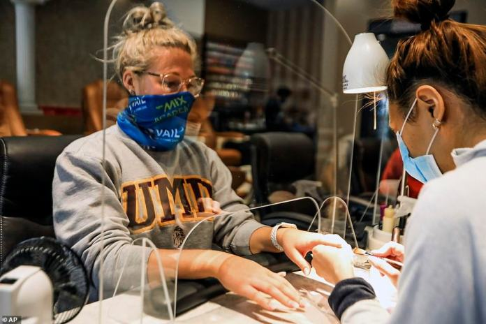 Logan Nash, left, gets a manicure through an acrylic shield at Jazzy Nails in Avon, Colorado on Monday