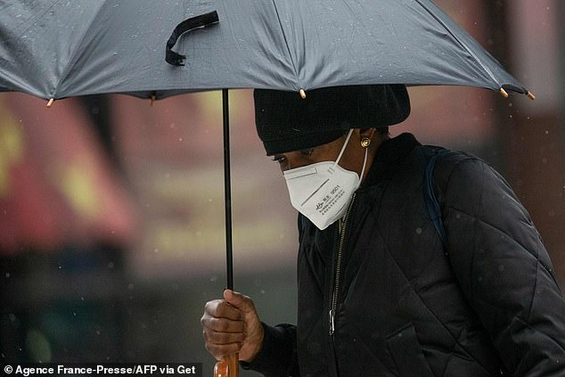 A woman wearing a face mask covers herself in the rain while walking down the street amid the coronavirus pandemic in New York earlier this month