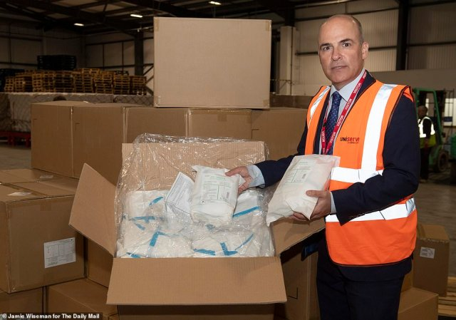 4. Ready for inspection: The Daily Mail's Arthur Martin with packets of white coveralls inside the warehouse