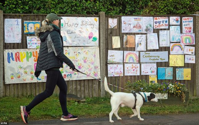 A woman walks her dog past cards and messages outside the home of Second World War veteran Captain Tom Moore as he celebrates his 100th birthday