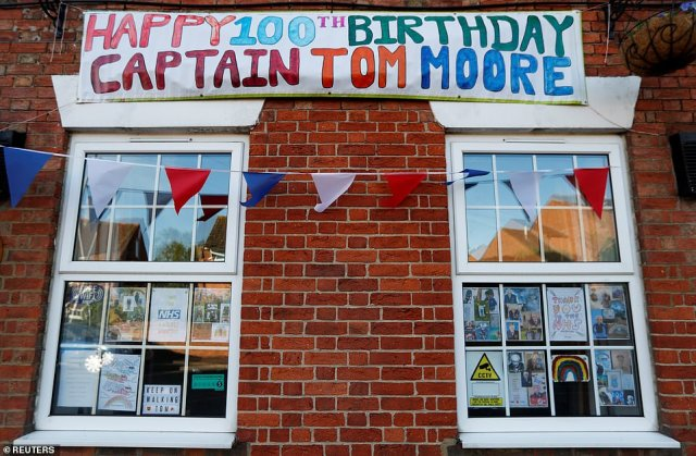 A banner marking 100th birthday of army veteran Captain Tom Moore hangs above windows, ahead of the Royal Air Force
