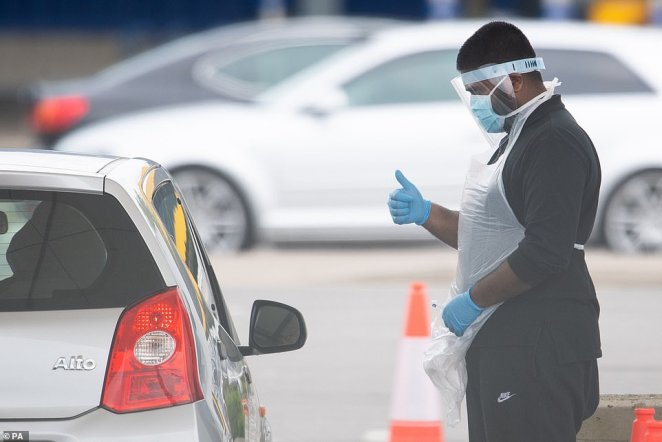 A worker gestures to someone arriving for a test at a centre in Wembley, London yesterday