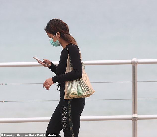 Australia's coronavirus tracing app has so far been downloaded five million times (pictured, a woman uses her mobile phone while walking at Bondi Beach on April 3)